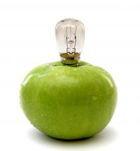 Green apple with a lamp isolated over white background